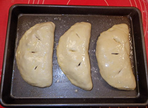Calzone ready for the oven with a light coating of olive oil and slits to vent steam.