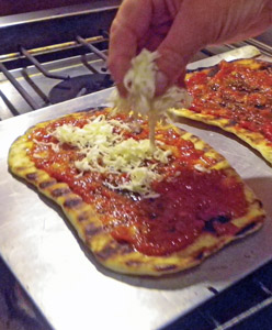 Grated homemade mozzarella is sprinkled on the pizza.